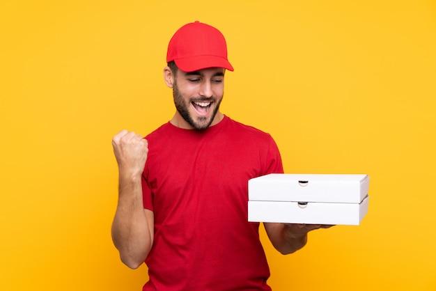 Uomo che tiene le scatole di pizze sul muro isolato