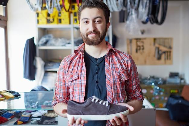 Uomo che tiene le sue nuove scarpe da ginnastica