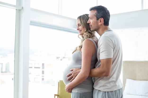 Uomo che tiene lo stomaco della donna incinta in camera da letto
