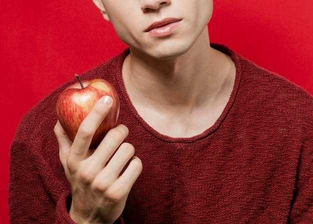 Uomo che tiene mela nella mano destra