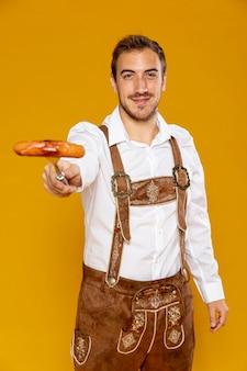 Uomo che tiene salsiccia tedesca con fondo giallo