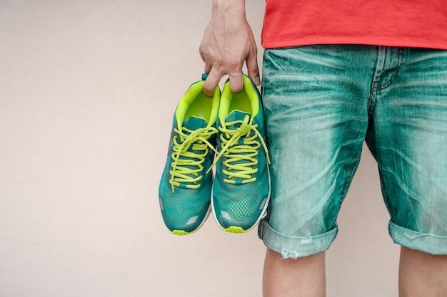 Uomo che tiene scarpe sportive in mano.