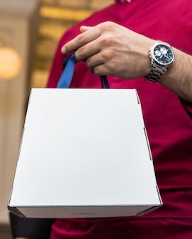Uomo che tiene scatola bianca