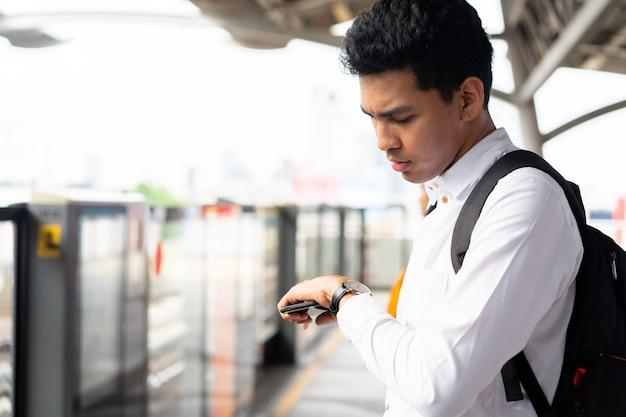 Uomo che tiene smartphone e alla ricerca di guardare a portata di mano per il controllo del programma orario del treno alla stazione