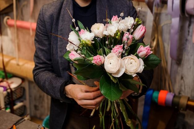 Uomo che tiene un bellissimo mazzo di fiori