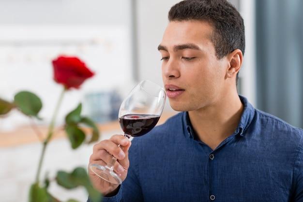 Uomo che tiene un bicchiere di vino rosso