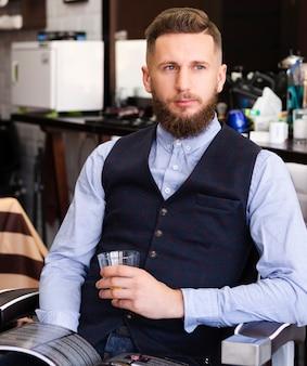 Uomo che tiene un bicchiere di whisky presso il negozio di barbiere