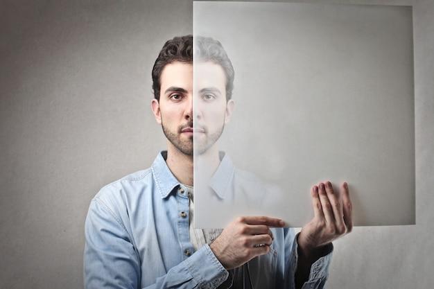 Uomo che tiene un foglio trasparente davanti alla sua faccia