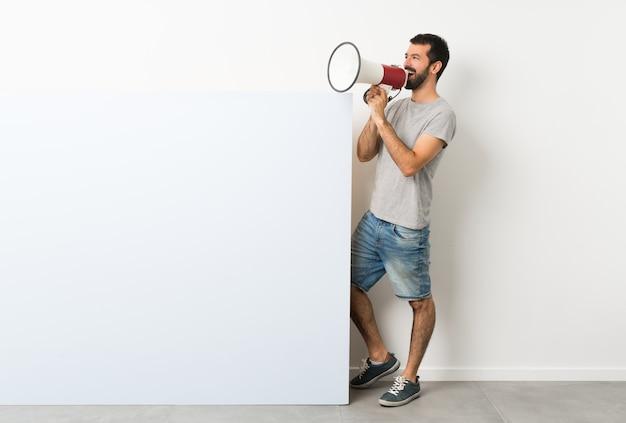 Uomo che tiene un grande cartello vuoto e che grida tramite un megafono