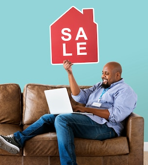 Uomo che tiene un'icona di vendita di casa