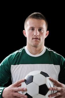 Uomo che tiene un pallone da calcio su sfondo nero