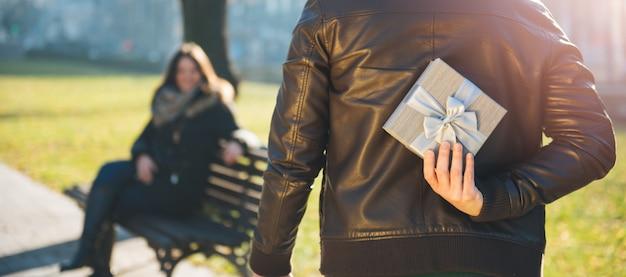 Uomo che tiene un regalo dietro la schiena