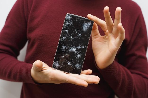 Uomo che tiene un telefono cellulare dopo un incidente. telefono digitale con schermo rotto.