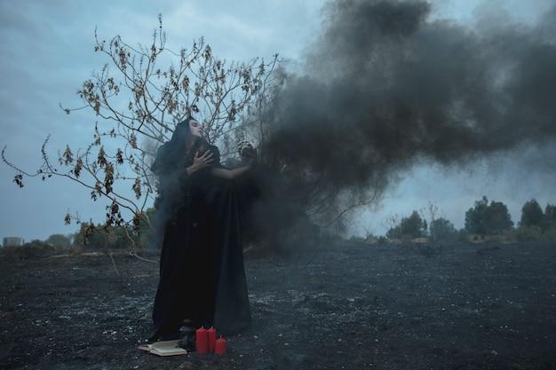 Uomo che tiene un teschio in una nebbia nera