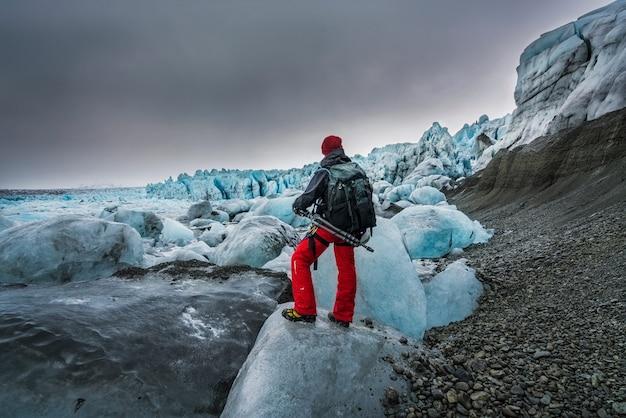 Uomo che tiene un treppiede contemplando gli iceberg