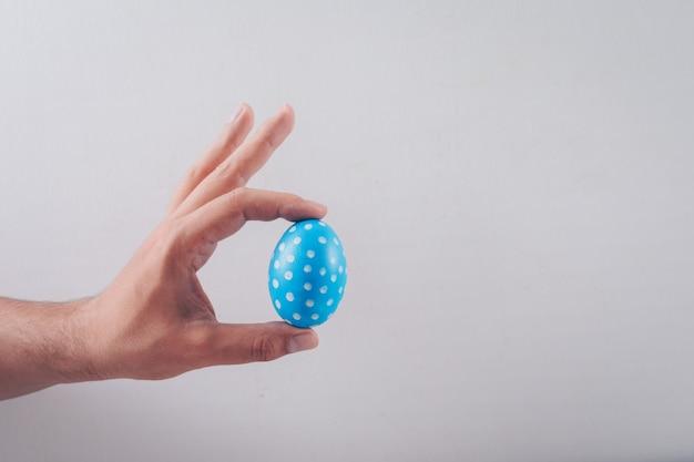 Uomo che tiene un uovo di pasqua su sfondo bianco.
