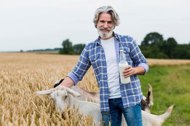 Uomo che tiene una bottiglia di latte di capra