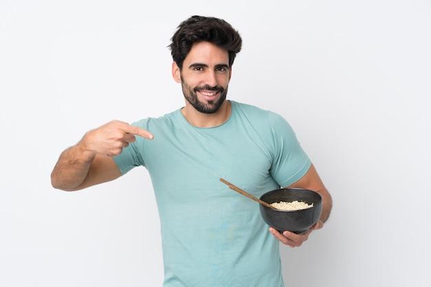 Uomo che tiene una ciotola piena di noodles sul muro isolato
