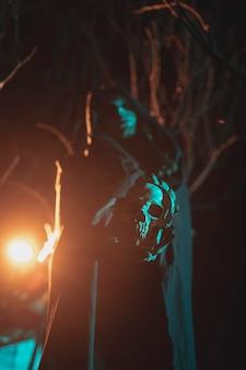 Uomo che tiene una lanterna e un teschio nella notte