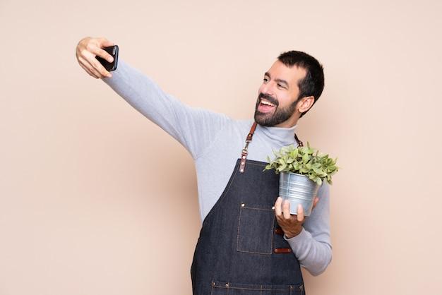 Uomo che tiene una pianta che fa un selfie