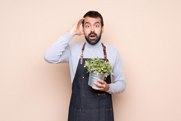 Uomo che tiene una pianta con espressione sorpresa