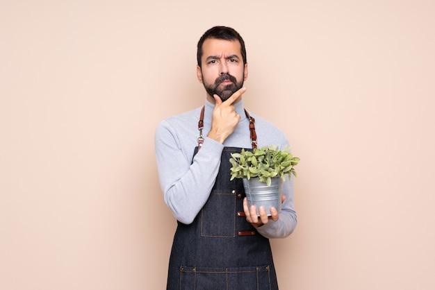 Uomo che tiene una pianta sopra il pensiero isolato