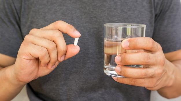 Uomo che tiene una pillola e un bicchiere d'acqua.