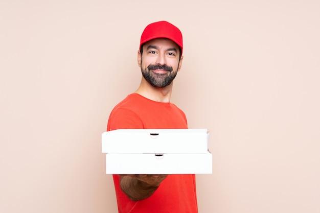 Uomo che tiene una pizza sopra fondo isolato