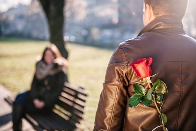Uomo che tiene una rosa rossa dietro la schiena