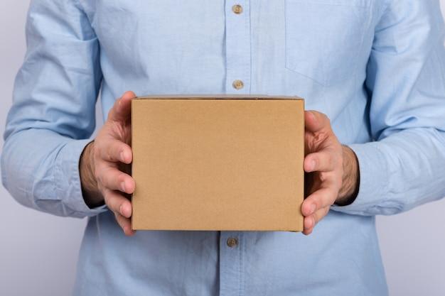 Uomo che tiene una scatola di cartone. servizio di consegna. avvicinamento. copia spazio. modello.