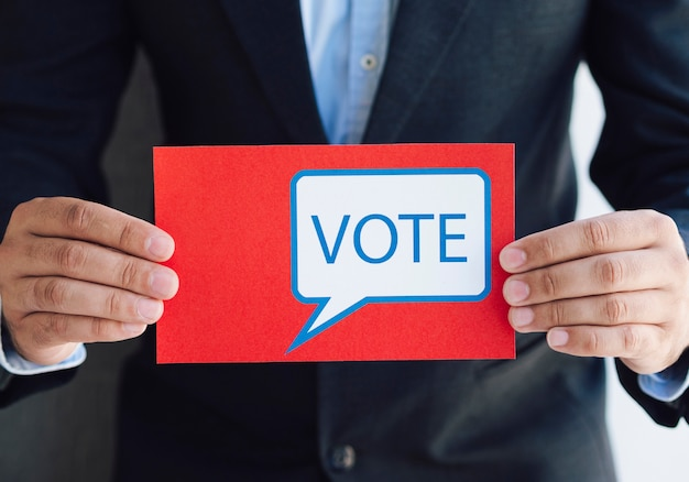 Uomo che tiene una scheda elettorale con un messaggio di voto