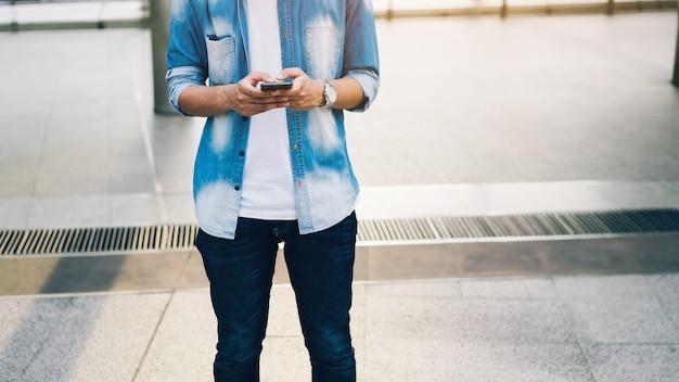 Uomo che tiene uno smartphone. usando il cellulare sullo stile di vita. tecnologia per il concetto di comunicazione.