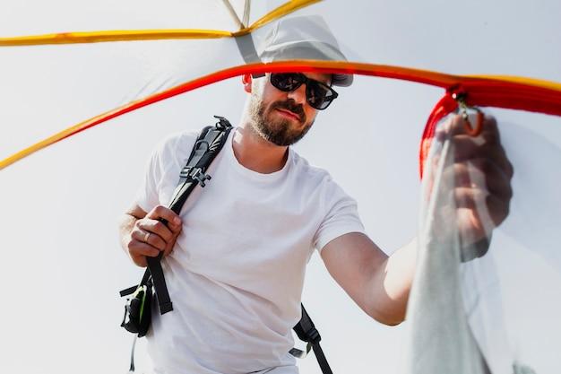 Uomo che tira la cerniera della tenda per entrare all'interno