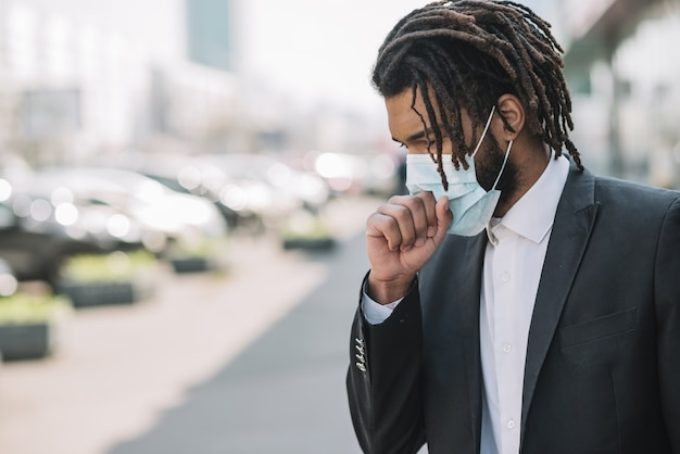 Uomo che tossisce e indossa una maschera medica