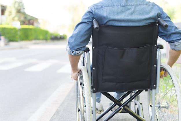 Uomo che usa la sua sedia a rotelle in una città