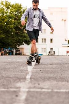 Uomo che usa la tazza di smaltimento mentre pratica i rollerskate