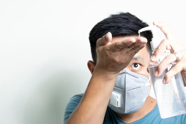 Uomo che usando cura di pelle sporca dei batteri del virus disinfettante della mano di lavaggio pulito del gel dell'alcool su fondo bianco