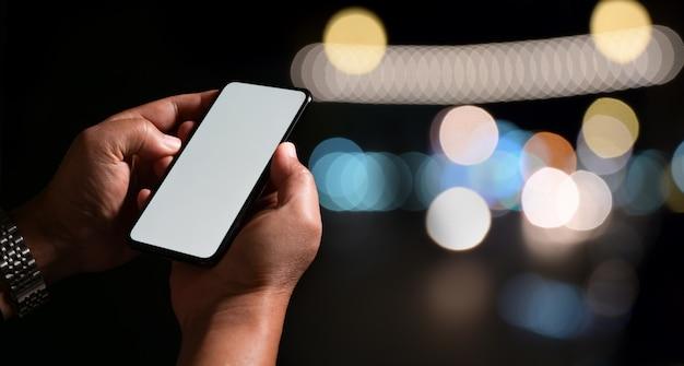 Uomo che usando il suo fondo mobile del bokeh della luce notturna dello smart phone