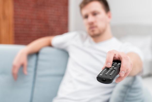 Uomo che usando il telecomando per cambiare il primo piano dei canali
