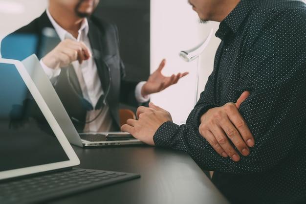 Uomo che usando l'auricolare voip con tavoletta digitale e computer e smart phone latop in ufficio moderno