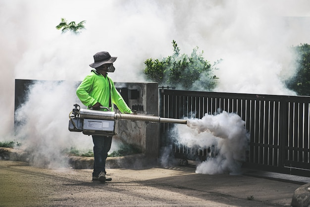 Uomo che usando la macchina della nebbia per controllare pericoloso dalle zanzare