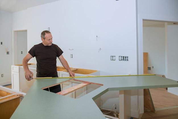 Uomo che usando la misura di nastro per misurare sul bancone della cucina in legno dentro per il miglioramento domestico.