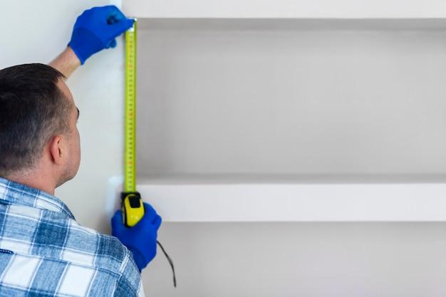 Uomo che usando la misura di nastro su una parete