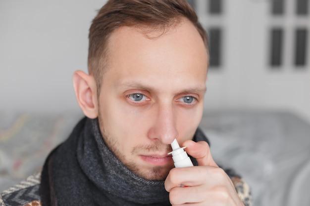Uomo che usando spray nasale.