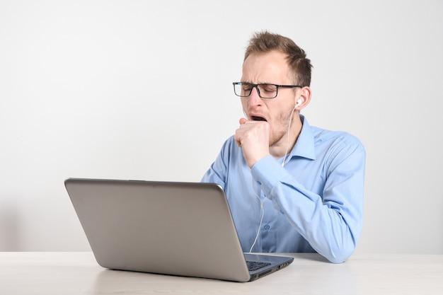 Uomo che utilizza computer portatile a casa nel salone. l'uomo d'affari maturo invia l'e-mail e lavora a casa. lavoro a casa. digitando sul computer con documenti e documenti sul tavolo.