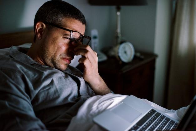 Uomo che utilizza computer portatile su un letto