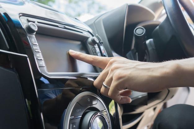 Uomo che utilizza il controllo del sistema di auto che spinge il touch screen del pulsante del pannello