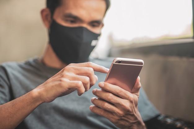 Uomo che utilizza il telefono cellulare a casa, uomo asiatico tenendo il telefono nella caffetteria