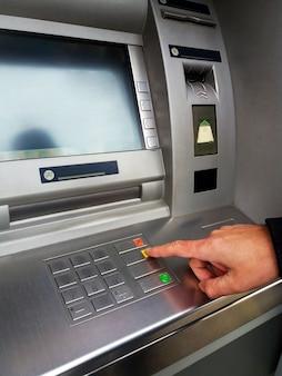 Uomo che utilizza la bancomat con carte bancarie e immettere codice pin / pass sul tastierino.