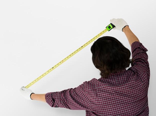 Uomo che utilizza la misura della regola del nastro studio